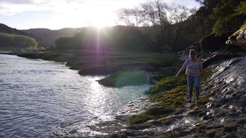 A young woman walks along the slippery bank of a river. video