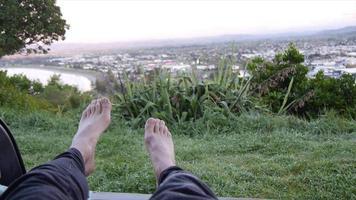 pov des jambes et des pieds d'un homme couché campant à l'arrière de son véhicule suv au-dessus d'une ville. video