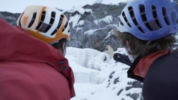 Two men point and discuss a climbing route for ice climbing on a frozen waterfall in the mountains. video