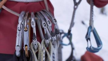 Close-up of carabiners on a climbing harness belt on an ice climber in the mountains. video