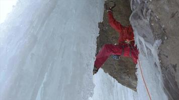 A man ice climbing on a frozen waterfall in the mountains. video