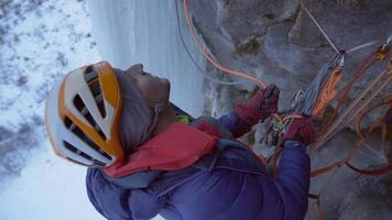 A man belays while ice climbing on a frozen waterfall in the mountains. video