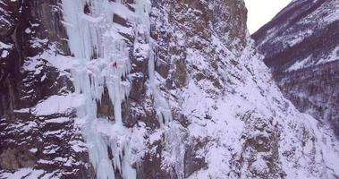 Aerial drone view of a man ice climbing on a frozen waterfall in the mountains. video