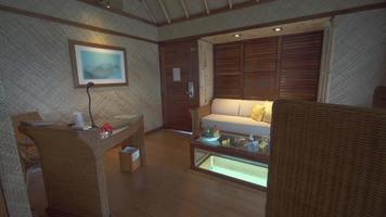 una sala de estar interior de hotel resort de lujo en un bungalow sobre el agua con una mesa de café con piso de vidrio. video