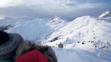 un uomo e una donna coppia in piedi in cima a uno stile di vita di montagna nella neve d'inverno. video