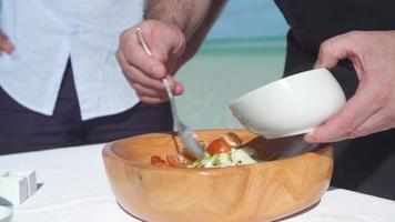 A man puts dressing on a poke salad lunch in a bowl. video