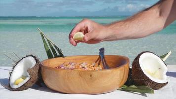 A man squeezing lemon on a poke salad lunch in a bowl. video