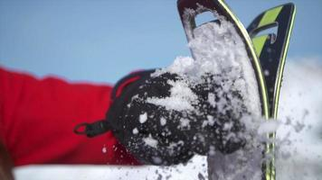 A woman brushes snow off her skis with glove to go skiing in the snow at a ski resort. video