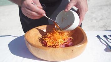 un hombre prepara un almuerzo de ensalada poke con atún ahi y zanahorias en un cuenco. video
