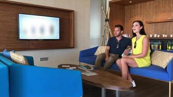 una pareja de hombre y mujer se relaja en la sala de estar de la habitación de su hotel resort. video