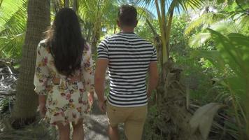 un couple homme et femme marchant sur un chemin dans les îles tropicales de la polynésie française. video