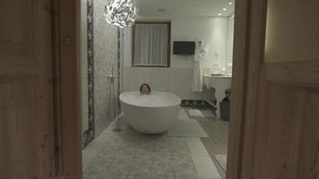 A woman enjoys a bubble bath in a bathtub at a luxury resort. video
