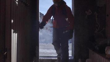 un hombre sale de un refugio de cabaña de esquí en montañas cubiertas de nieve. video