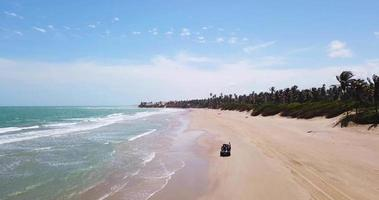 Aerial drone view of a 4x4 jeep car vehicle driving on the beach surf trip. video