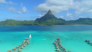 Aerial drone view of a luxury resort, overwater bungalows and sailboat in Bora Bora tropical island. video
