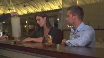 Ein Mann und eine Frau, die in einer Bar in einem tropischen Inselresort ein sehr kaltes Getränk trinken. video