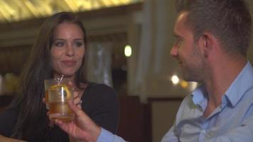 Ein Mann und eine Frau, die in einer Bar in einem tropischen Inselresort auf ein kaltes Getränk anstoßen. video