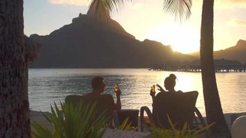 A man and woman couple toasting and drinking drinks at a tropical island resort with the lagoon and Mount Otemanu. video