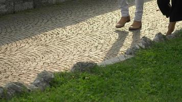 A man and woman couple walking on a cobblestone street, Italy, Europe. video