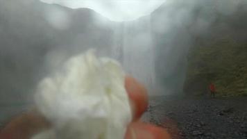 un fotógrafo limpiando la lente de su cámara cerca de la cascada skogafoss en islandia, europa. video