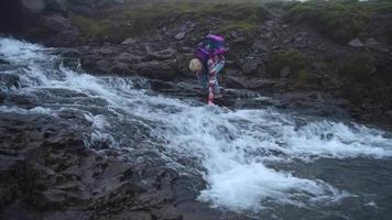um homem caminhando perto de um rio e bebendo água na Islândia, na Europa. video