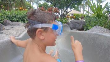 un ragazzo gioca su uno scivolo d'acqua scivolo in una piscina in un resort dell'hotel. video