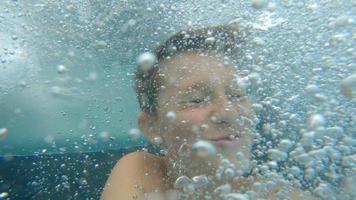 un niño juega en un tobogán de agua en una piscina en un hotel resort. video