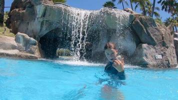 un ragazzo gioca in una cascata in piscina in un resort dell'hotel. video