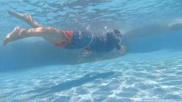 un ragazzo gioca e nuota sott'acqua in una piscina in un resort dell'hotel. video