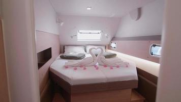 Interior view of a master bedroom on a sailboat boat and towel swan art. video
