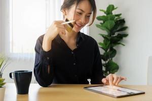 mujer joven con tableta para compras en línea foto