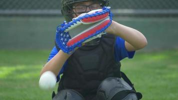 Boy catcher dropping ball with American flag glove in a little league baseball game, red, white, blue, stars. video