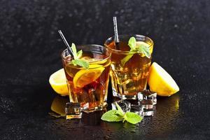 dos vasos con té helado tradicional frío con limón, hojas de menta y cubitos de hielo. foto