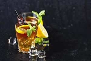 Té helado tradicional con limón, hojas de menta y cubitos de hielo en dos vasos sobre fondo negro húmedo. foto