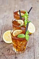Té helado tradicional con limón, hojas de menta y cubitos de hielo en tres vasos en la mesa de madera rústica. foto