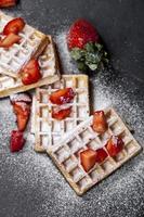 Obleas de Bélgica con fresas y azúcar en polvo en la pizarra. foto