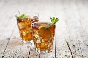 Dos vasos con té helado tradicional con limón, hojas de menta y cubitos de hielo en vidrio sobre fondo de mesa de madera rústica. foto