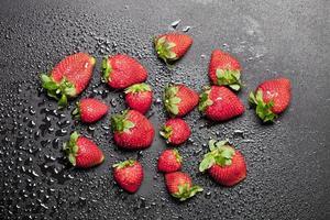 Fresa madura fresca con gotas de agua sobre fondo negro. foto