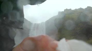 A photographer cleaning his camera lens near Skogafoss waterfall in Iceland, Europe. video