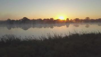Aerial drone view of a sunset sunrise over a lake with fog in Africa. video