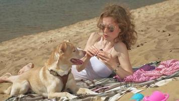 uma jovem na margem do rio tomando sorvete com seu cachorro video