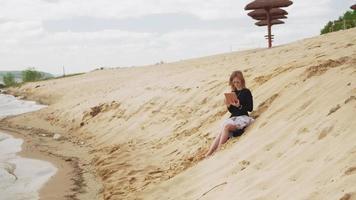una donna che usa un tablet in spiaggia video