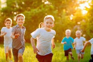 un grupo de niños felices de niños y niñas corren en el parque sobre el césped en un día soleado de verano. foto