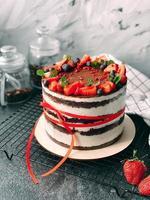 Delicioso y jugoso pastel casero decorado con fresas y bayas vivas. foto