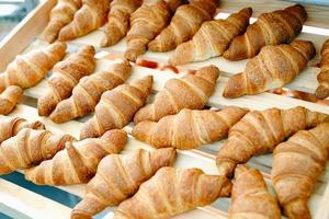 Fresh croissants with cream on a wooden shelf. photo