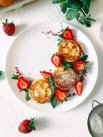 tortitas caseras de tartas de queso con fresas en un plato. foto