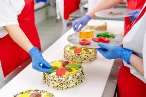 Decorating cakes on the conveyor of a confectionery factory. photo