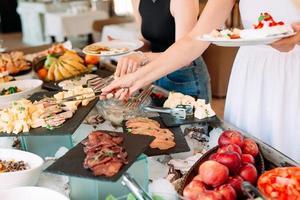 mano de personas toman comida buffet en el restaurante del hotel. foto