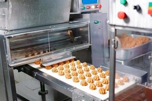Sweets production and industry concept - chocolate candies processing on conveyor at confectionery shop. photo