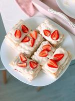 Milky cake with cream and strawberries and cup of coffee photo
